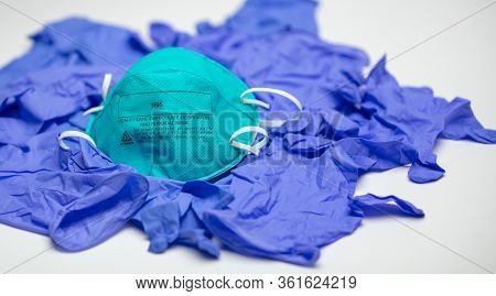 A Turquoise N95 Particulate Respirator And Surgical Mask On Top Of Many Medical Gloves.