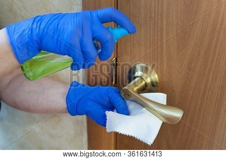 Woman Hand Is Applying Sanitizer On The Door Handle. Cleaning Door Handle With Alcohol Spray For Cov