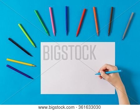 A Hand With A Blue Marker On A White Sheet And A Set Of Markers On A Blue Background. Universal Mark
