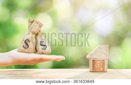 Man Hand Hold Money Bag With Presenting And Home Model And Gold Coin With Growing Interest In The Pu