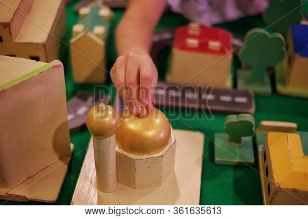 A Child Adding A Wooden Mosque Block To Her Modeled City With Road, Buildings And Trees