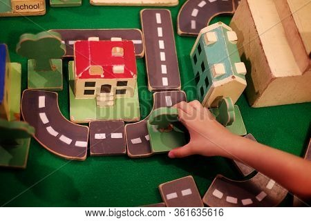 Top View Of A Kid Building A City From Wooden Blocks With Trees, Roads And Buildings.