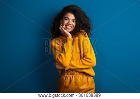 Photo of a beautiful smiling optimistic young african woman posing isolated over blue wall background.