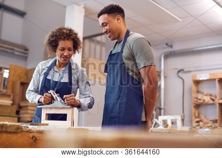 Female Tutor With Carpentry Student In Workshop Studying For Apprenticeship At College
