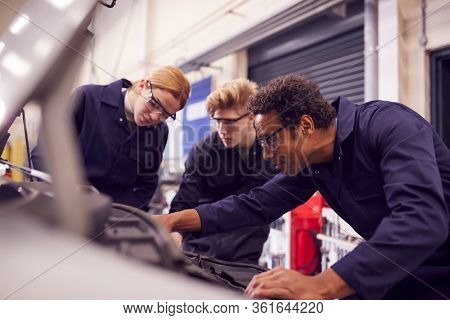 Male Tutor With Students Looking At Car Engine On Auto Mechanic Apprenticeship Course At College