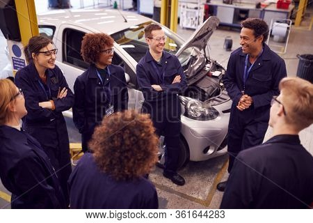 Male Tutor With Students Teaching Auto Mechanic Apprenticeship At College