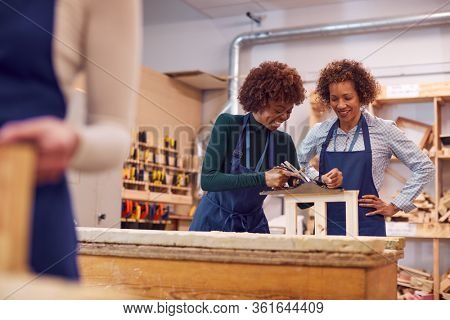 Tutor With Female Carpentry Student In Workshop Studying For Apprenticeship At College
