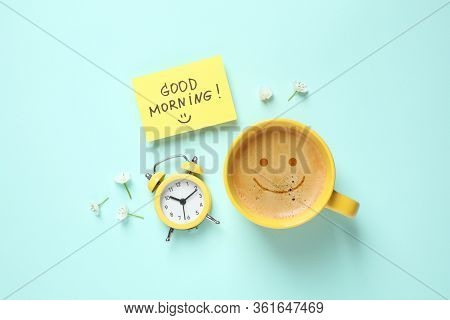 Delicious Coffee, Alarm Clock And Card With Good Morning Wish On Light Blue Background, Flat Lay