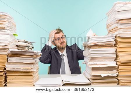 Shocked Businessman Sitting At The Table With Many Papers In Office, He Is Overloaded With Work - Im