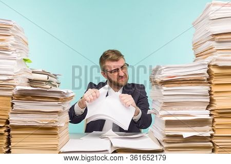 Business Executive Working In The Office And Piles Of Paperwork, He Is Overloaded With Work. Breaks