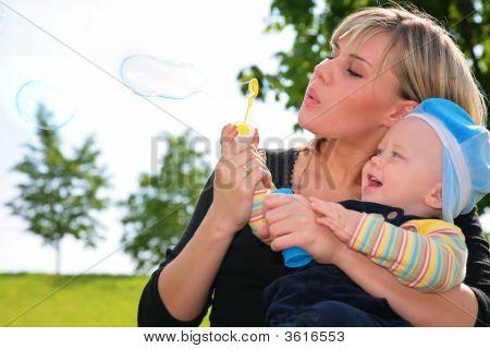 Mãe com uma criança infla bolhas de sabão
