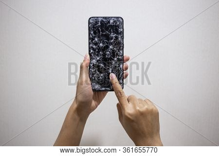 Woman Hands Holding Smartphone With Broken Or Cracked Screen On White Background. Not Available To U