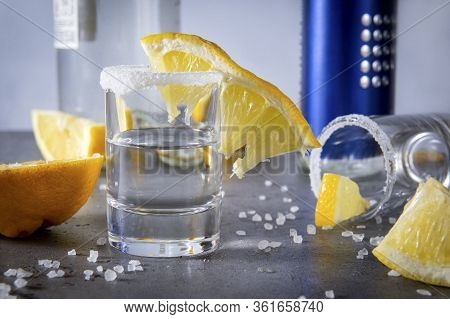 Glass Of Silver Tequila With Salt And Lemon Slices On A Gray Background, Bottles In The Background,