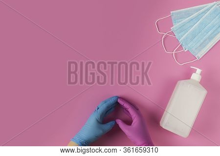Protective Medical White Face Mask And Sanitizer Gel On A Pink Background, Success With A Heart Symb