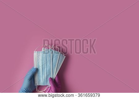 Doctor Holds Respiratory Surgical Face Mask In Hands Blue And Pink Medical Gloves On Pink Background