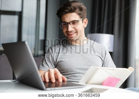 Image of a positive optimistic young man indoors at home using laptop computer holding documents.