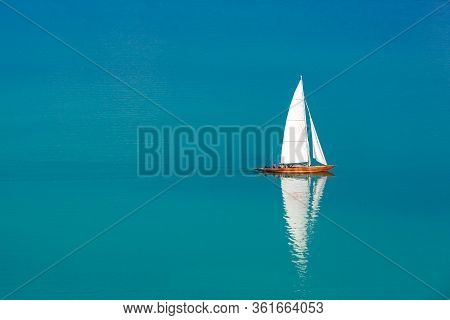 Sailing Yacht In The Endless Blue Sea, Amazing White Sail And Calm Water Reflection. Amazing Summer