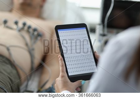 Close-up Of Female Cardiologist Holding Tablet And Examine Patients Heartbeat. Person Laying On Hosp