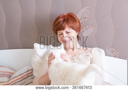 Pleasant Senior Woman With Short Red Hair In Home Clothes Is Sitting On The Bed And Petting A Cute W
