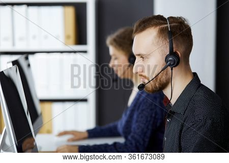 Red-bearded Businessman Talking By Headset Near His Female Colleague While Sitting In Modern Office.