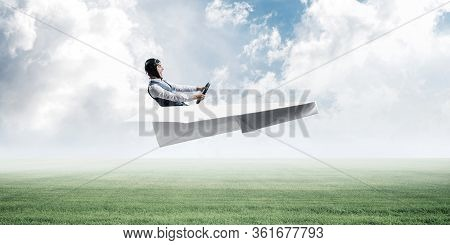 Happy Aviator Driving Small Paper Plane On Background Of Natural Landscape. Man In Big Paper Airplan