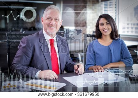 Portrait Of Smiling Experienced Mentor And Young Female Employee With Virtual Marketing Charts. Busi