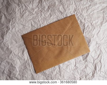 Envelope Of Kraft Paper Lies On Crumpled Paper. Note From A Paper On A Cord Of An Envelope From Kraf