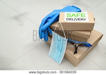 Safe Delivery Of Packages To Your Home. Cardboard Boxes, Medical Mask, Safety Glasses And Rubber Glo