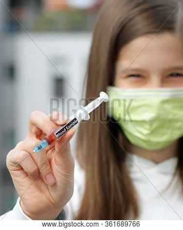 Hand Of Young Nurse Wears Surgical Mask With Syringe Containing Blood Sample For Analysis In Hospita