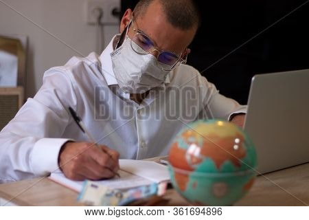 Man Working On Laptop While Taking Notes. Businessman Working At Home With Computer While Writing On