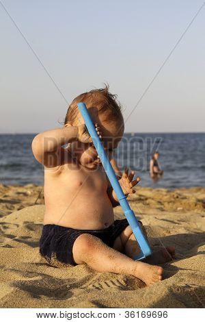 Baby playing with the sand on a beach