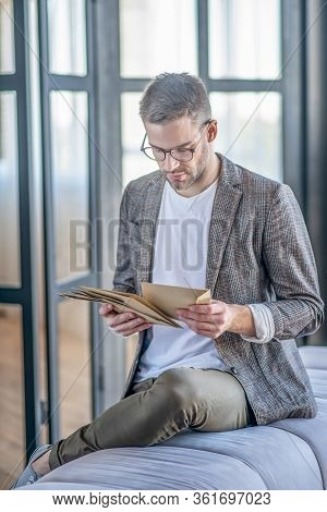 Stylish Fair-haired Man Holding Papers In His Hands