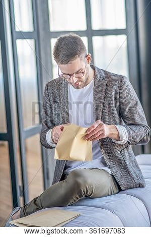 Stylish Fair-haired Man Looking Involved While Opening The Envelope