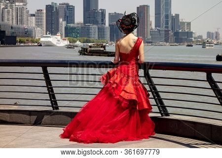 Shanghai, China - April 13, 2017: The Bride Dressed In A Bright Red Dress In Shanghai Near The Huang