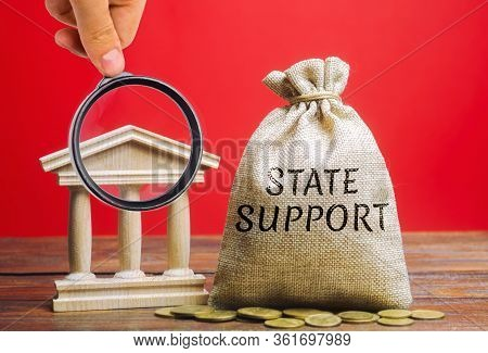 Money Bag With The Word State Support And The Bank Building. Tax Relief. Protection Of Manufacturers