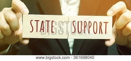 Businessman Collects Puzzles With The Words State Support. Tax Relief. Protection Of Manufacturers I