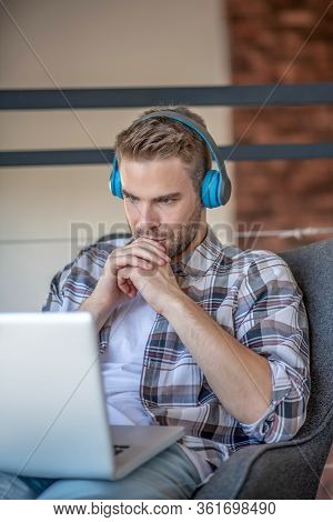 Young Man With Headphones Looking Involved And Serious