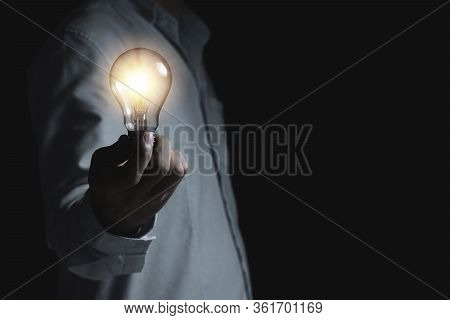 Businessman Holding Lightbulb Which It Glowing On Black Background And Copy Space .creativity Idea C