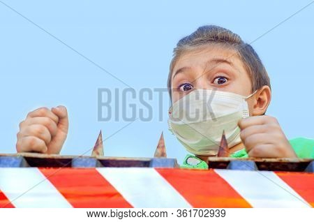 Frightened Boy In A Protective Mask Peeps Out From Behind A High Fence With Spikes And A Signal Tape