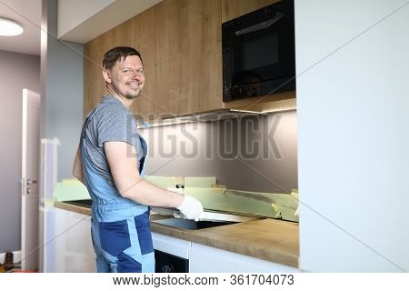 Happy Man In Work Clothes Sets Hob In Kitchen. Installation An Induction Hob Above Oven. Work In Acc