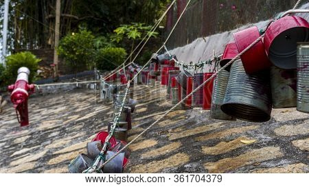 Hong Kong - January 1 2020 : Chain Of Tin Cans, Red And Silver Tin Cans Hanging On The Rope In Tai O