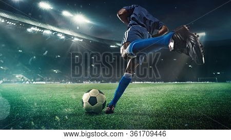 Professional Football Or Soccer Player In Action On Stadium With Flashlights, Kicking Ball For Winni