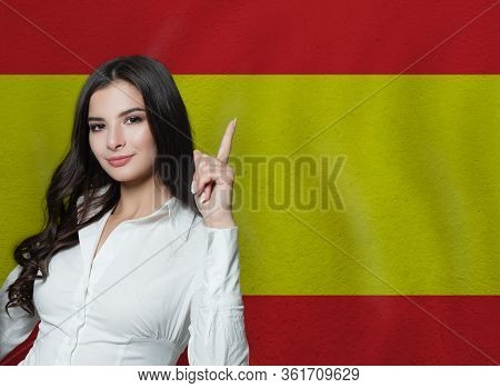 Woman Pointing Up On Spanish Flag Background. Education Or Business Concept