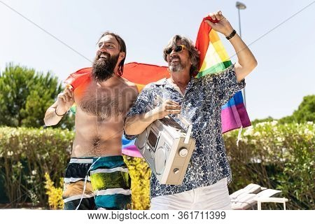 Father And Son Holding A Gay Flag And Having Fun. Pensioner Man Having Fun Outdoors.two Friends Enjo