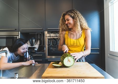 Two Female Bloggers Recording Preparation Of Melon At Home.