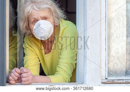 A Sad Elderly Wrinkled Woman Breathes Fresh Air Through The Window In The Respiratory Mask Of Her Ho