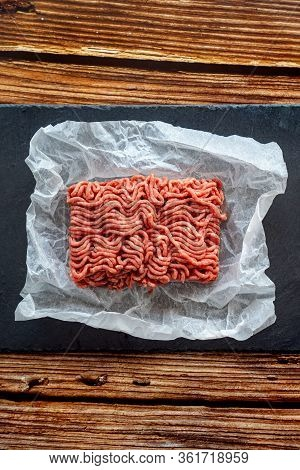 The Minced Meat On The Cooking Paper And Stone Tray On A Wooden Table. Prefabricated Patties.