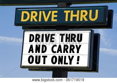 Horizontal Shot Of A Drive Thru Sign That Says Drive Thru And Carry Out Only!  Blue Sky Behind It.