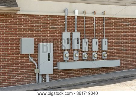 Horizontal Shot Of Electric Meters For A Commercial Strip Center Mounted On A Red Brick Wall.