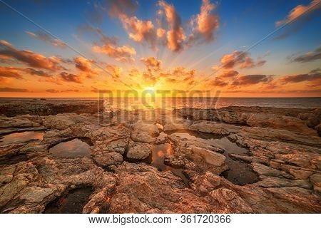Beautiful Colorful Sunset Near The Sea At Cyprus With Dramatic Clouds And Boulders. Reflections In T
